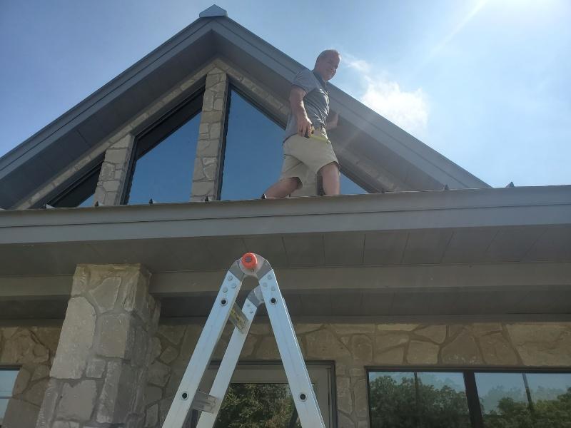 Brett on a roof doing window tinting